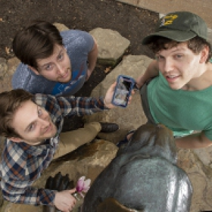 three young men standing next to the Panther statue on campus, looking up. One is holding a phone with the app on the screen