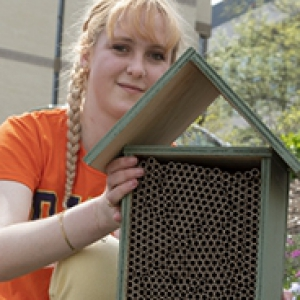 young woman with pigtail braids holding a bee house