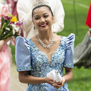 young woman dressed in a blue dress and white headpiece