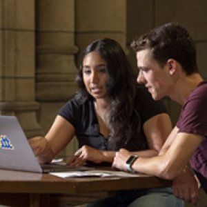 Two people sitting at a table looking at a laptop together