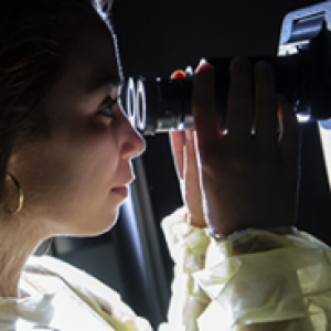 A person in gold earrings and a yellow top looks through an eyepiece