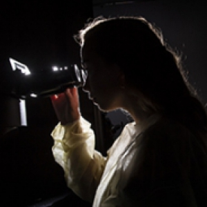 Woman in a lab coat looking into a microscope