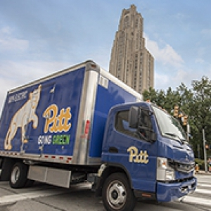 Blue box truck with panther, script Pitt logo, going green and 100% electric painted on it, with Cathedral of Learning in the background