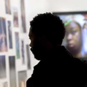A person's silhouette looking at an art display