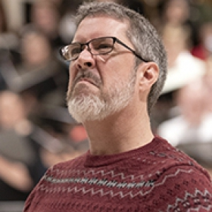 Scott O'Neal in a red sweater in front of a choir