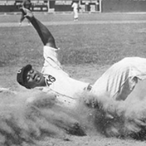 Josh Gibson sliding home in a baseball uniform