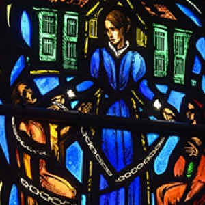 a woman in a long blue dress depicted in stained glass