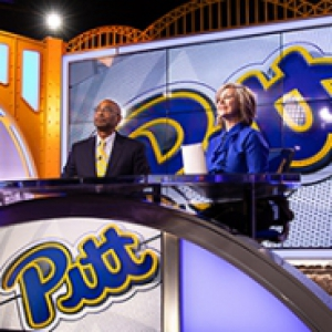 "Two people sit at a desk with ""Pitt"" emblazoned on the front"