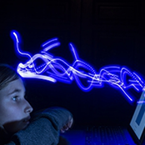 Teen sits on the computer in the dark, with blue light beaming from it
