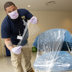 Man in mask and gloves applies plastic covering to a chair