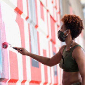 a person in a sports bra painting on a wall with a roller dipped in reddish paint