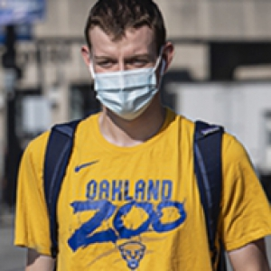 A person in a yellow t-shirt and face mask walks on campus