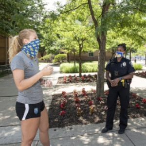 Two police officers in face masks talk to a person in a gray t-shirt and shorts