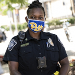 A police officer in a Pitt face mask standing next to a person in a gray shirt