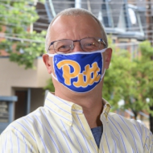 A man in a Pitt face mask and striped shirt