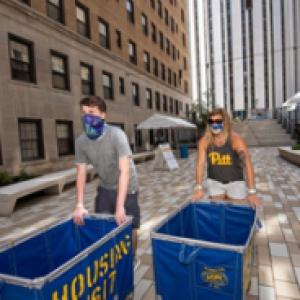 Two students push Pitt carts
