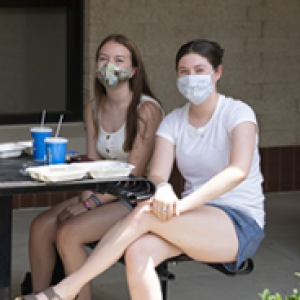 Three people sit at a table outdoors with face masks and food in front of them