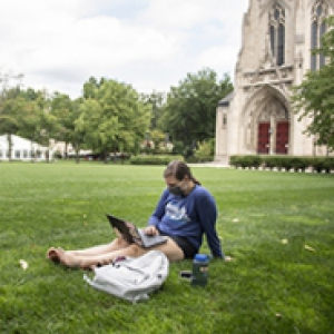 A person in a face mask uses a laptop while sitting on the lawn in front of Heinz Chapel
