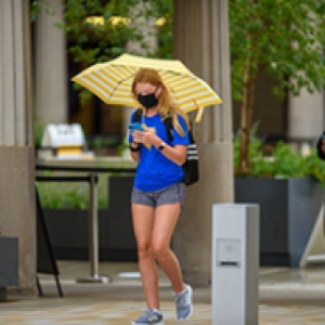 A student in a blue shirt walks down the sidewalk in a face mask and holding an umbrella and phone