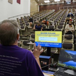 An instructor in a purple shirt teaches a lecture to a mostly empty classroom of masked students