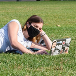 A student in a face mask on a laptop while laying down in a field