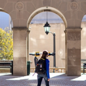 A person in a blue jacket and black backpack walks on campus