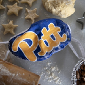 A blue Pitt face mask lying on a table surrounded by cookie dough and cookie cutters