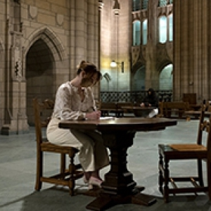 A person in a white outfit studies at a table in the Cathedral of Learning