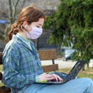 A person in a plaid shirt and pink face mask sits on a bench with a laptop