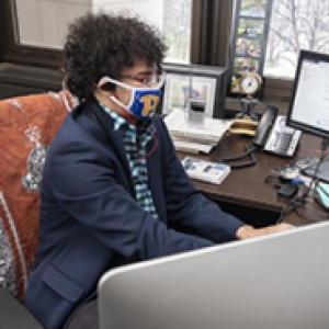 Abdesalam Soudi in a face mask, headphones and a blue jacket, at a computer