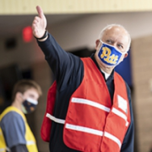 A person in an orange vest and blue face mask points to their right