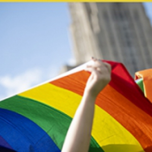 Hand holding rainbow flag, Cathedral of Learning in the background