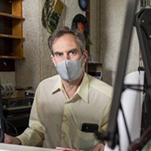 Greg Weston with a grey mask and yellow shirt sits at a red desk with recording equipment in the foreground