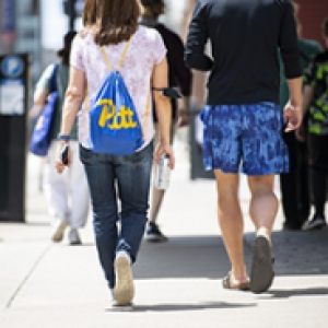 Two students walking down a sidewalk form behind, one wearing a blue Pitt bag