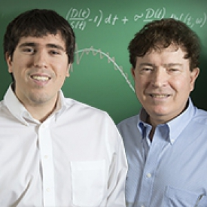 father and son standing in front of a green chalkboard
