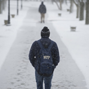 A person with a Pitt backpack and a winter hat walks away from the camera on a snowy campus