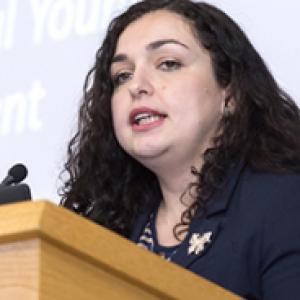Vjosa Osmani speaking at a podium in a dark top