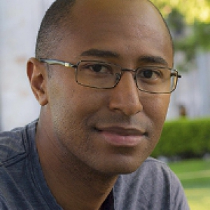 Cameron in a blue-gray shirt and thin wire glasses