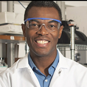 Portrait of Tagbo Niepa, wearing safety glasses, with lab equipment on shelves in background