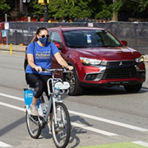 A person in a blue shirt and face mask bicycles on the street