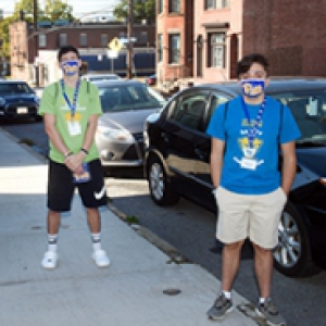 Three students stand on a sidewalk with face masks
