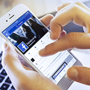 Close up of a person's hand holding a smart phone displaying Facebook, with a laptop computer in the background.