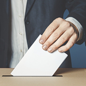 Person's hand placing a ballot in a slot in a voting box