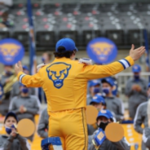 A person in yellow Pitt gear raises their hands in front of a band