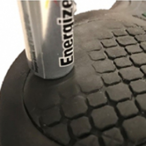 A battery on top of a shoe sole.