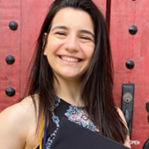 Brooke Pantano holding a graduation cap in front of a red door