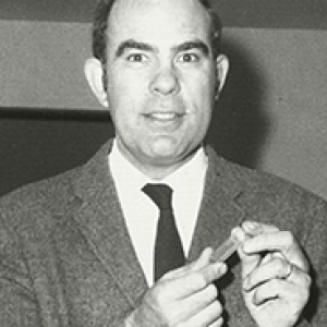 a black and white photo of Hapke in a suit, holding a vial of moon dust