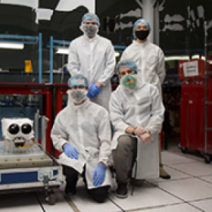 four people dressed in masks, gloves and white suits standing in a room of equipment
