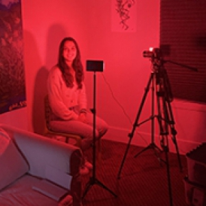 A person sitting in the corner of a dark red room with a camera facing them