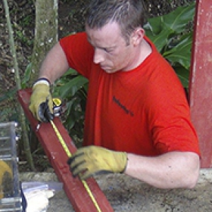 man in red shirt with work gloves with tools outdoors in Panama